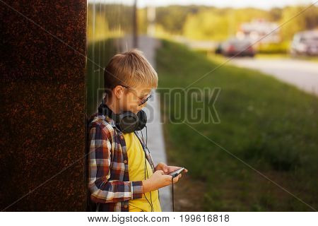 Handsome teenage boy in plaid shirt listening to music and using phone in summer day