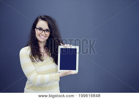 Surprised young woman using holding a digital tablet.