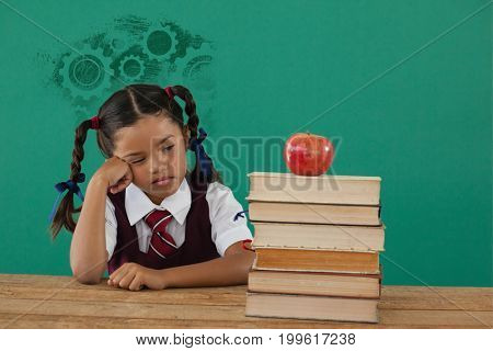 Digital composite image of gears on black spray paint against unhappy schoolgirl looking at books stack and apple against chalkboard