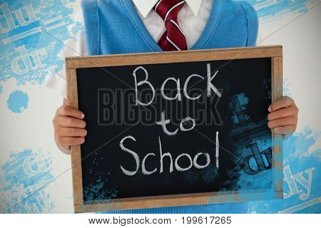 Digital composite image of equations against schoolboy holding writing slate with text back to school against white background