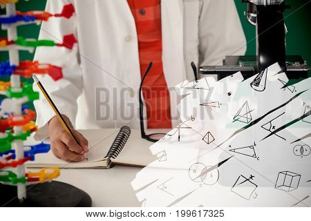 Various geometric shapes on black scribbling against schoolboy writing on book against green background