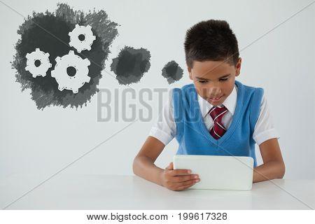 Digital composite image of gears on blue spray paint against schoolboy using digital tablet