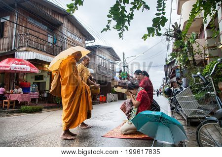 CHIANG KHAN, THAILAND - September 10, 2016 : Tourists offering sticky rice to Buddhist monk the morning on September 10, 2016 at Chiang Khan, Loei, Thailand.