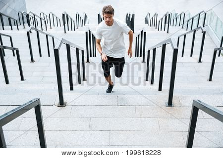 Image of young sports man running by ladder at the stadium outdoors and looking aside.