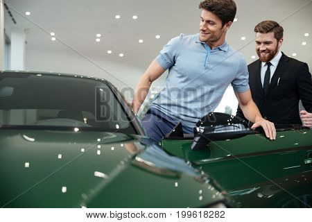 Young male customer getting inside his new car at the dealership