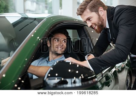 Professional male dealer selling car to a customer at the dealership