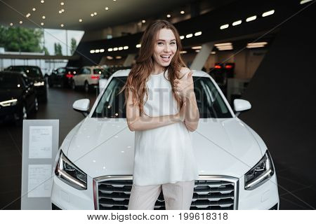 Image of amazing young happy woman standing near car in car dealership. Looking camera showing thumbs up.