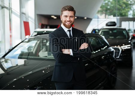 Smiling young male dealer in suit with arms folded standing in front of a new car at the dealership