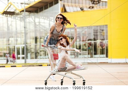 Two crazy smiling women in sunglasses having fun shopping trolley race outdoors