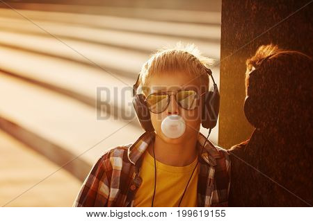 Teenage boy in sunglusses and headphone with bubble gum in summer sunset.