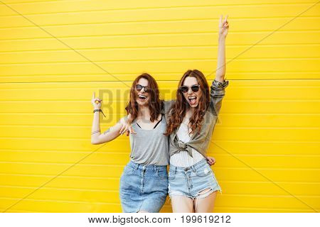Picture of two young cheerful women friends standing over yellow wall. Looking at camera.