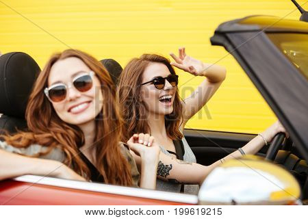Picture of happy two young women friends sitting in car over yellow wall.