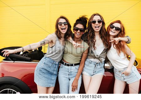 Image of happy emotional four young women friends standing near car outdoors. Looking camera.