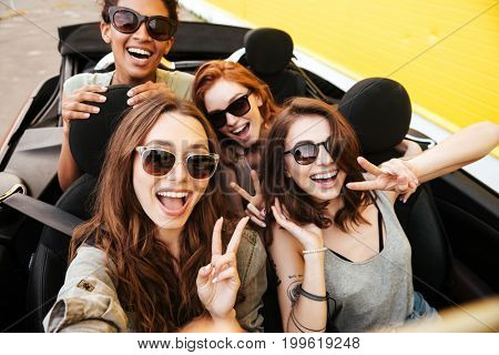 Picture of smiling emotional four young women friends sitting in car outdoors. Make selfie.