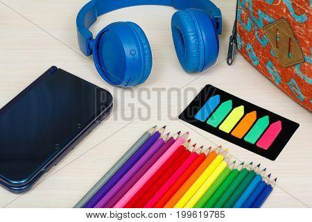 School Supplies. School Backpack, Book, Color Pencils, Ebook, Color Bookmarks And Headphones On Wood