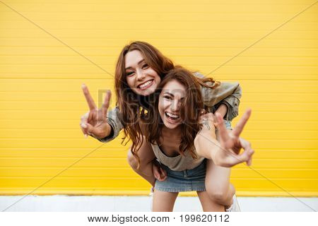 Picture of two young smiling women friends standing over yellow wall. Looking at camera showing peace gesture.