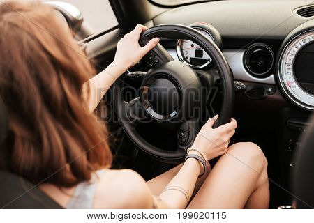 Back view photo of amazing young woman sitting in car outdoors.