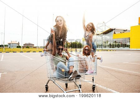 Image of young happy women friends have fun with shopping trolleys.