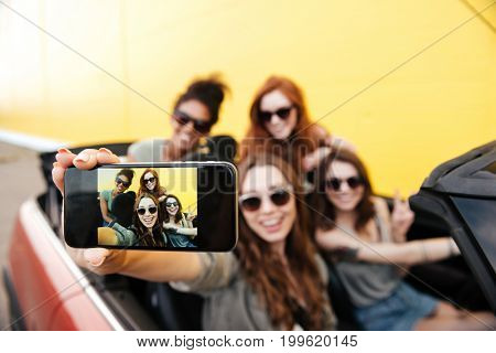 Picture of smiling emotional four young women friends sitting in car outdoors. Make selfie by phone.