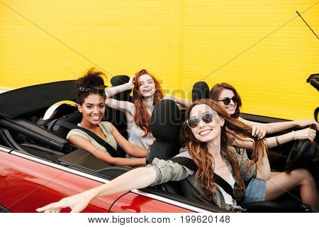 Image of happy emotional four young women friends sitting in car outdoors. Looking camera.