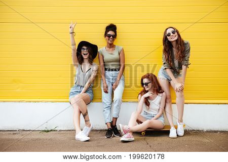 Image of four young smiling women friends standing over yellow wall. Looking at camera.