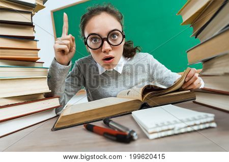Did you know that?! Curious student reads. Photo of astonished young girl wearing glasses pointing finger up. Education concept