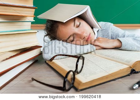 Tired young pupil fell asleep. Photo of young girl in school. Back to school!