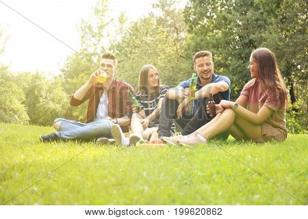 happy young friends enjoying picnic and eating