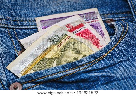Some bulgarian bank notes - just around 8 euro or 10 US dollars - in worn blue classic jeans pocket - macro capture with blur focus
