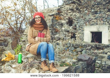 Beautiful young woman reading book in the park and enjoying sunny weather. Lifestyle and autumn concept.