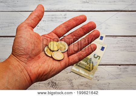Male pauper hand asking for alms - just few euro coins on the palm rough skin. Crisis poverty concept. Close up capture.