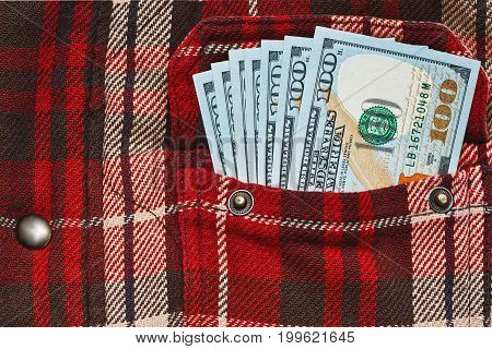 Salary wages in work warm checkered shirt pocket - few hundreds of US dollars honestly earned money. Close up capture new bank notes.