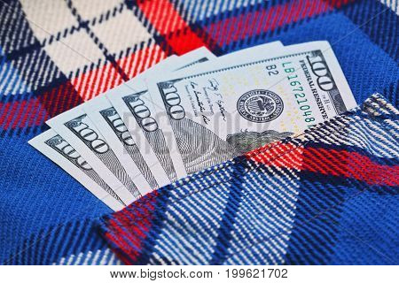 Few hundreds od US dollars in work checkered shirt pocket. Honestly earned salary or wages concept. Close up capture blur focus.