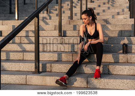 Picture of serious young sports lady sitting with earphones outdoors and looking aside.
