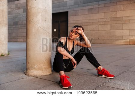 Image of concentrated young sports lady sitting with earphones outdoors.