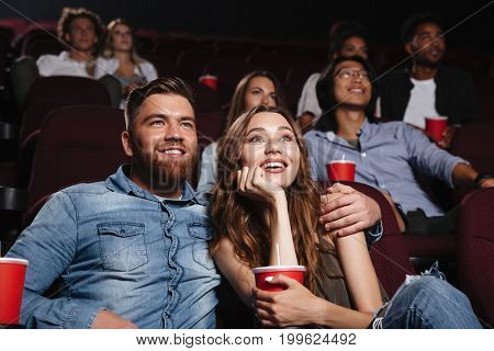Happy young couple sitting at the cinema and enjoys watching the movie