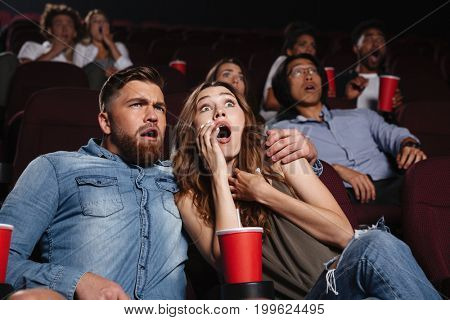 Shocked young couple watching a horror movie at cinema