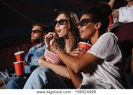 Two young women in eyeglasses watching 3d movie and eating popcorn while sitting in a cinema