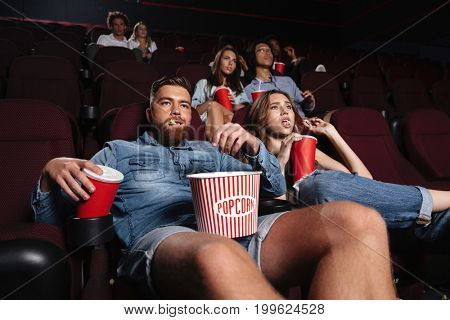 Impolite rude couple sitting in a cinema and chewing loudly while watching a movie