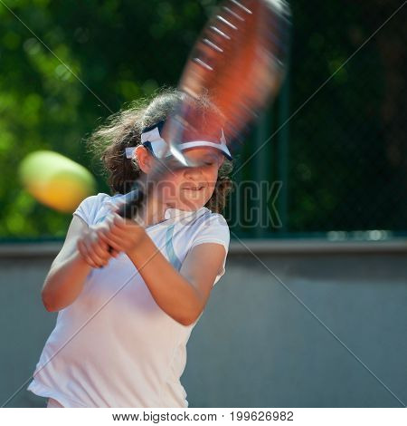 Junior Tennis Player  During Training Outdoors, Color Image, Focus On Girl