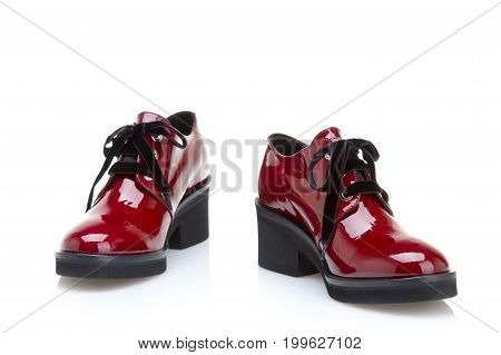 Red women's shoes with low heels made of patent leather on white background
