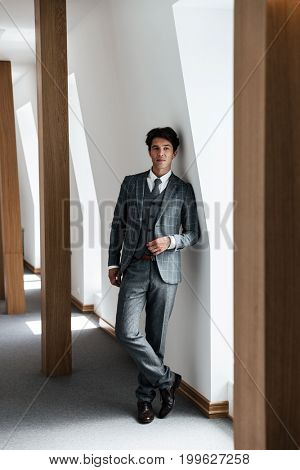 Full length of a successful businessman in suit posing and leaning on a wall indoors