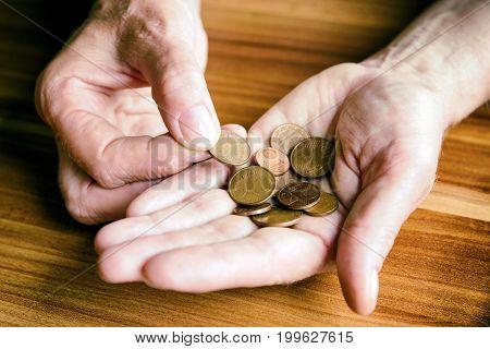 Euro coins in hand of senior. Conceptual photo.