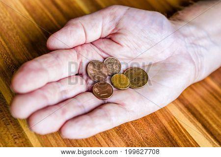 Euro coins in hand of senior. Conceptual photo