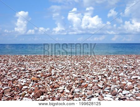 stone beach with blurred sea and sky