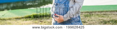 Pregnant young woman hugging her stomach outdoors