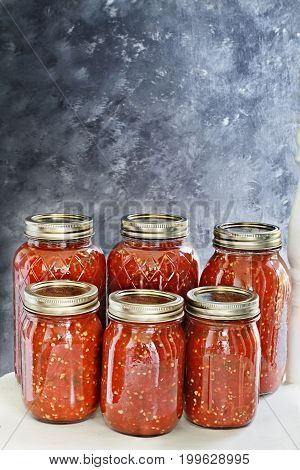 Mason jars canned with homemade salsa sitting on an old white country chair in front of a dark background. Shallow depth of field with selective focus on salsa.