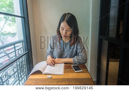 Young student writing notes, take note, doing homework on book