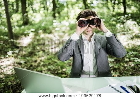 Tilt Up Image Of Young Businessman Using Binoculars In Office On Open Air. Male Executive Is Searchi