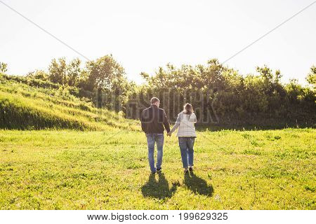 Man and woman holding hands and walking on country road.